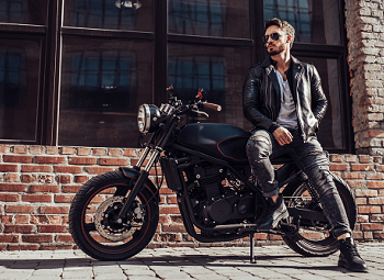 Man wearing a leather jacket and sunglasses leans against his motorcycle that is parked in front of the window of a brick building
